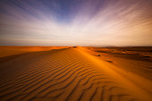 rippled sand dunes and 4 wheel tire tracks at sunset in wahiba sands desert in oman.