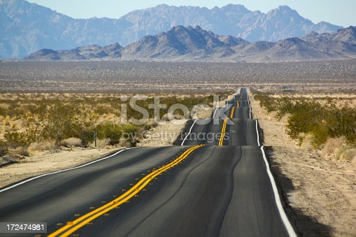 A very bumpy road along a highway in the Southern California desert.