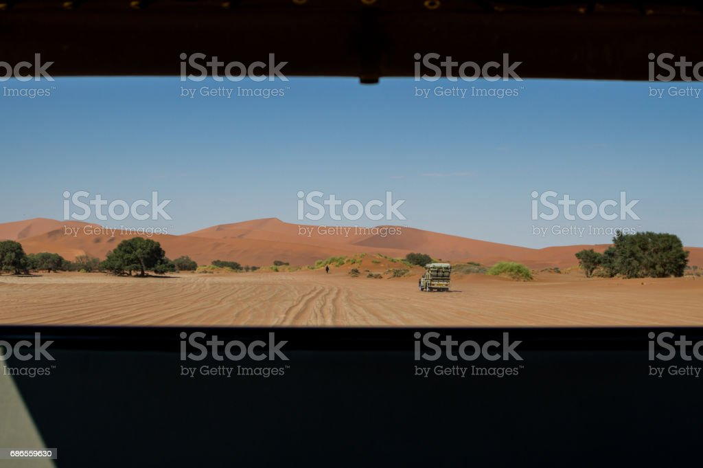 Desert Landscape with Dunes and Car seen from the Back of a Vehicle, Sossusvlei Namibia royalty-free stock photo