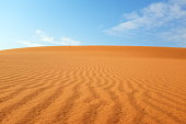 istock Desert landscape with orange rippled sand and clear blue sky 1194971539