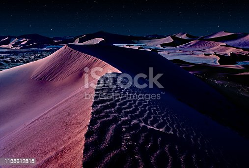 desert of namib at night with orange sand dunes and starry sky.