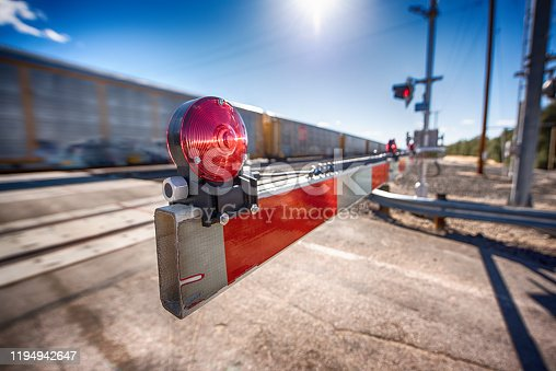 A railroad crossing with the gate closed as a freight train passes eastbound from Los Angeles through the Southern California desert at Kelso Junction located in the Mojave Desert in eastern San Bernardino County, California.