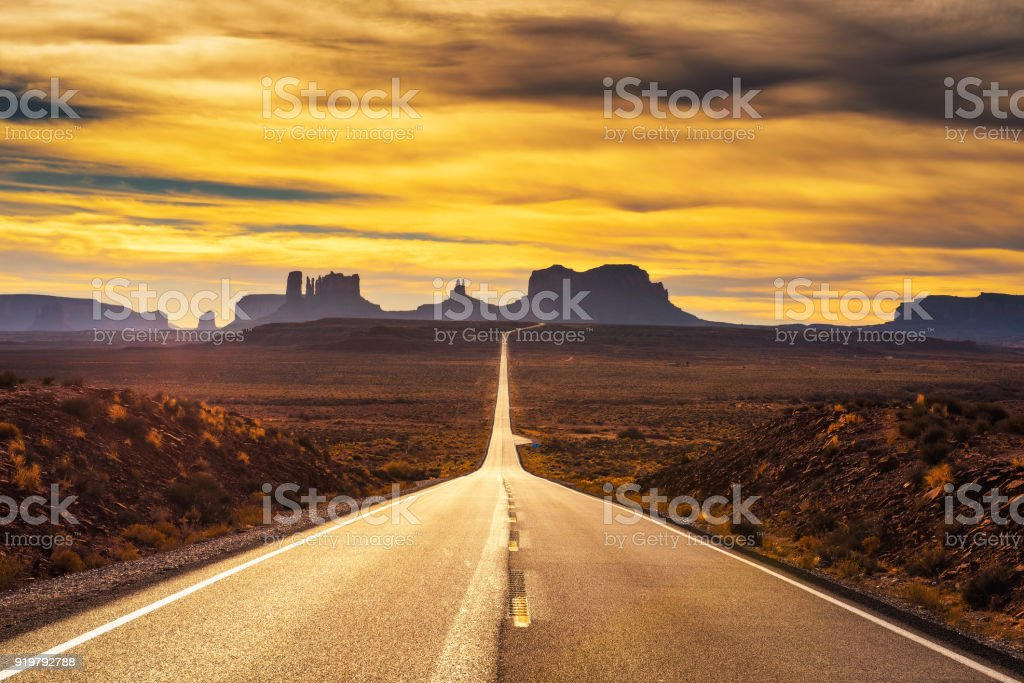 Desert road leading to Monument Valley at sunset foto stock royalty-free