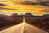 Desert road leading to Monument Valley photographed at the Forrest Gump Point with dramatic sunset sky.