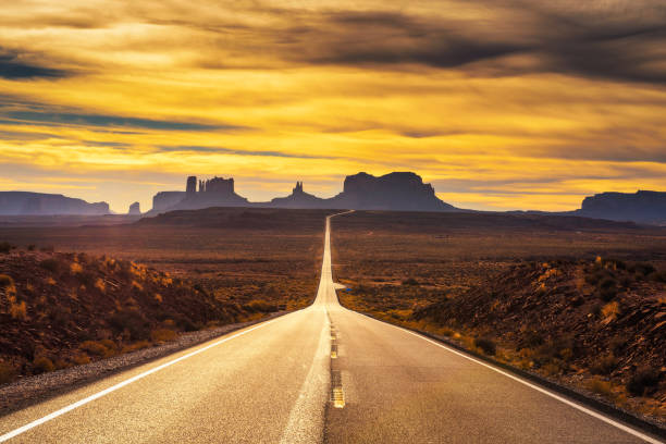 Desert road leading to Monument Valley at sunset Desert road leading to Monument Valley photographed at the Forrest Gump Point with dramatic sunset sky. wildlife reserve stock pictures, royalty-free photos & images