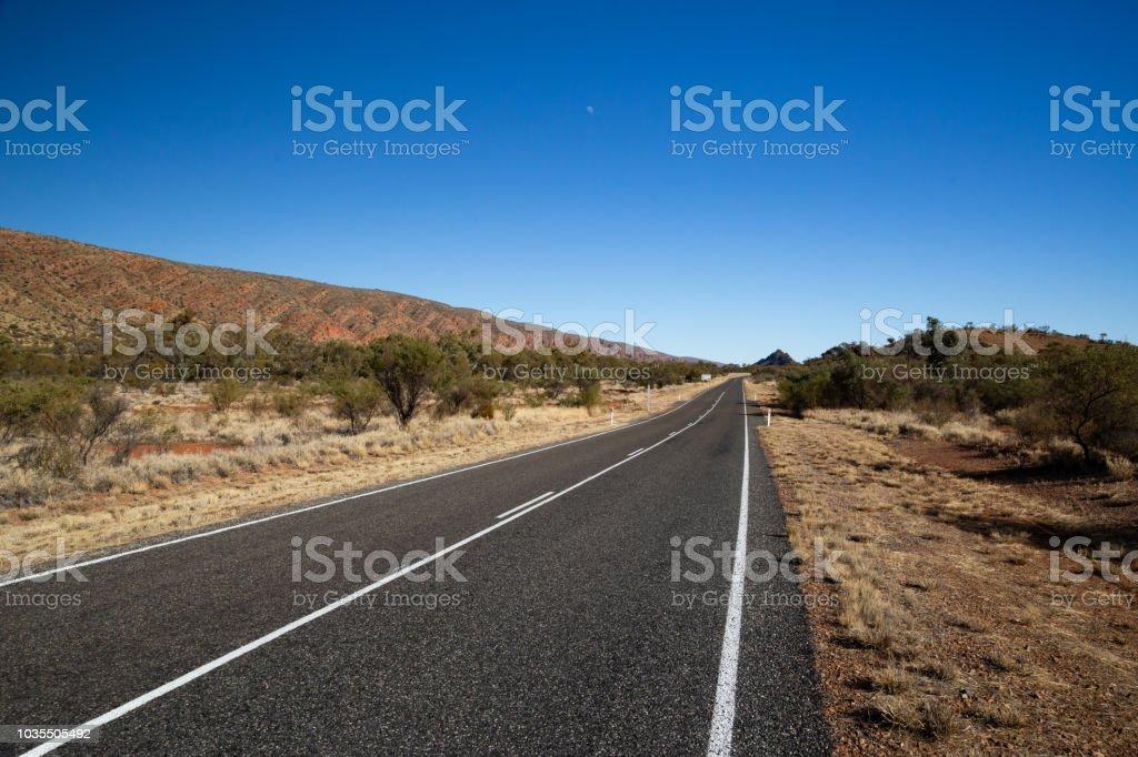 A desert road stretches through the Australian Outback stock photo
