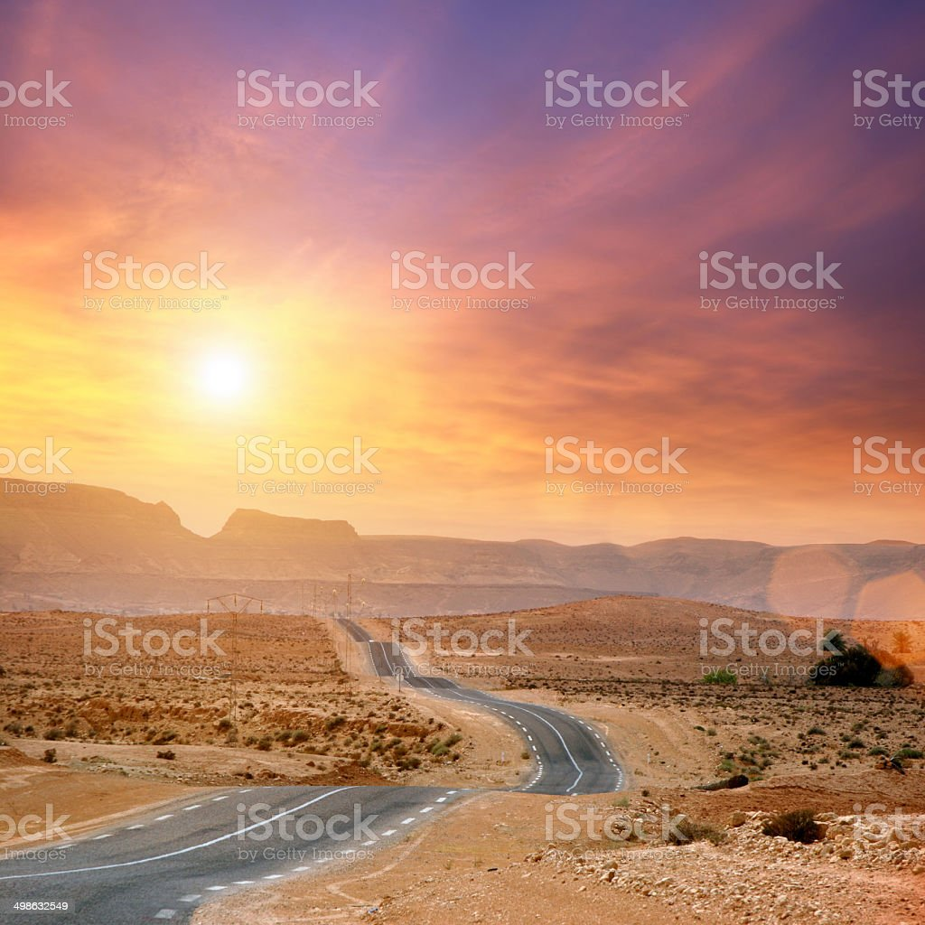 Desert road to sunset, going forward to the sun stock photo