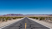 Desert road with patched up asphalt in California. Sunny day with Blue skies