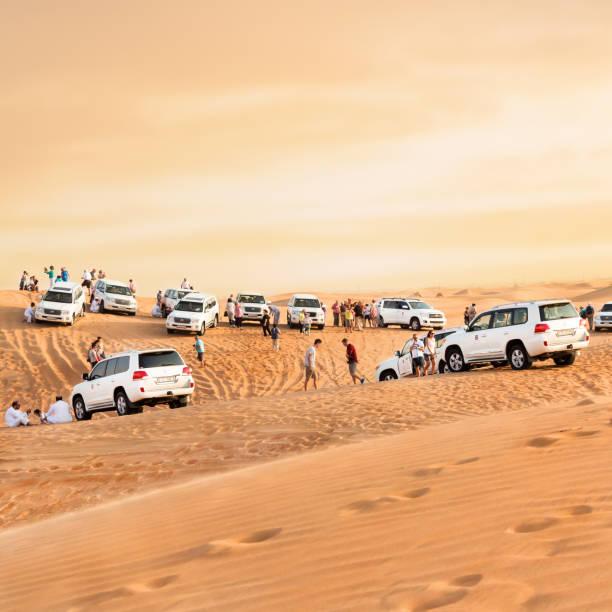 "Desert safari in Dubai DUBAI, UNITED ARAB EMIRATES - 31 Ott, 2016: Crowd in the desert.""nDesert that surrounds the city of Dubai. Group of tourists make a safari with 4x4 car in the desert dunes. quadrato stock pictures, royalty-free photos & images"