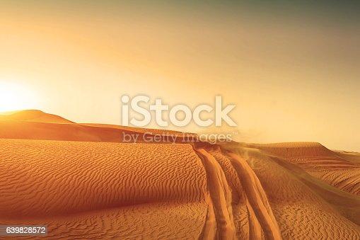istock Desert sand dunes road at sunset 639828572