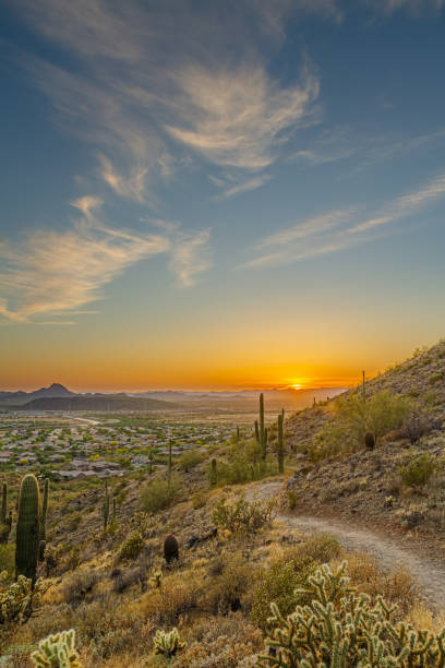 A desert trail on a mountain leading to a sunset over a valley in Phoenix stock photo