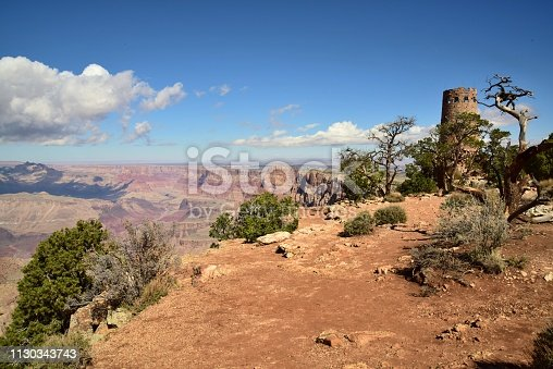 A sunlit view of the Desert View Watchtower and the muddy Colorado River from the Desert view area of the Grand Canyon.