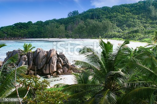 Blue sea and exclusive remote beach in Seychelles islands (La Digue) wih turquoise water and few people swimming and playing