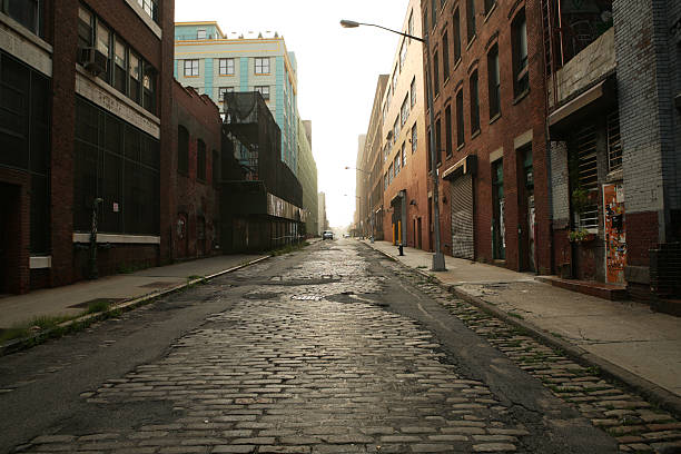 Deserted Brooklyn DUMBO Cobblestone Backstreet Morning Looking into the rising sun up a deserted Brooklyn, DUMBO, backstreet at dawn. derelict stock pictures, royalty-free photos & images