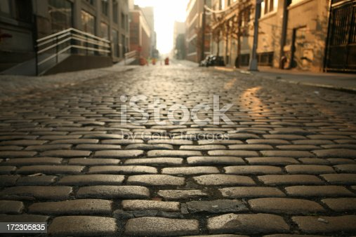 Cobblestone street in old Brooklyn near the waterfront district of DUMBO at dawn. Close focus on near cobblestones.