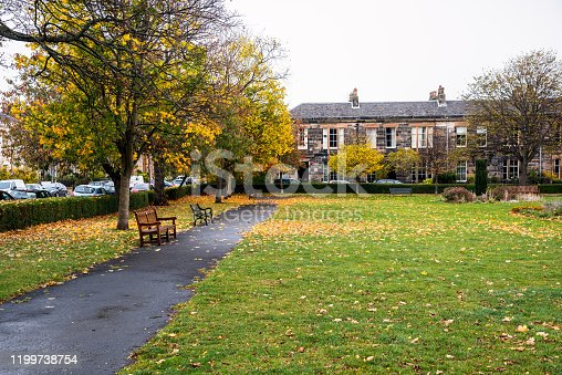 825525754 istock photo Deserted footpath lined with benches and deciduous trees in a public park in a residential district in autumn 1199738754