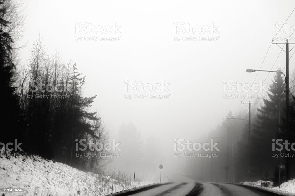 A deserted highway is in the fog in black and white stock photo