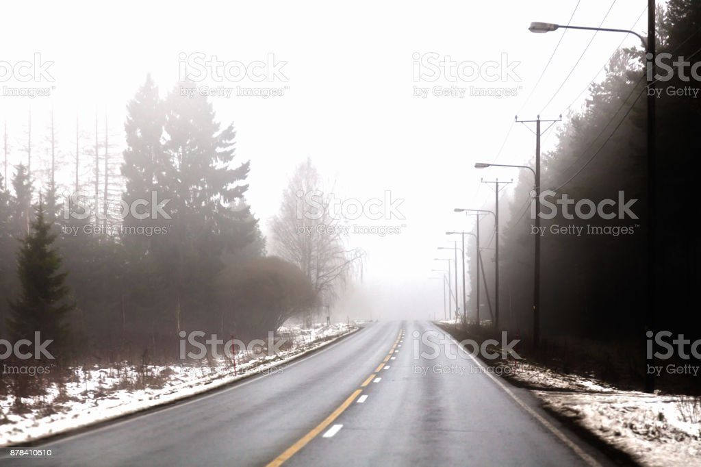 A deserted highway is in the fog stock photo