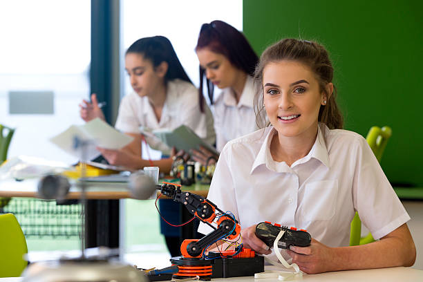 Design and Technology Lesson Adolescent girl in a design and technology lesson. She is smiling at the camera with a robotic arm that she is building infront of her. female high school student stock pictures, royalty-free photos & images