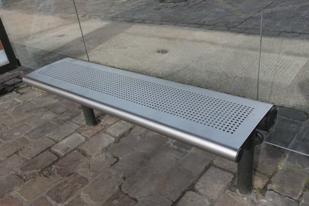 Cтоковое фото Design bench in stainless steel in a bus station sheltered by glass panels