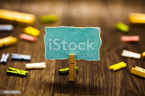 istock Design business concept Business ad for website promotion banners empty social media ad Clothespin holding blue paper note reminder clothespins wooden floor 1050208200