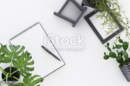 istock Design concept - top view of white A4 flipped paper with black clipboard, potted plant, cactus, frame and pen on white background. 3d rendering 1177581242