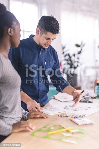 istock Design couple strategize in their modern studio 1024573964