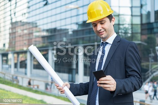 istock Design engineers is working at building site with phone 1029768122