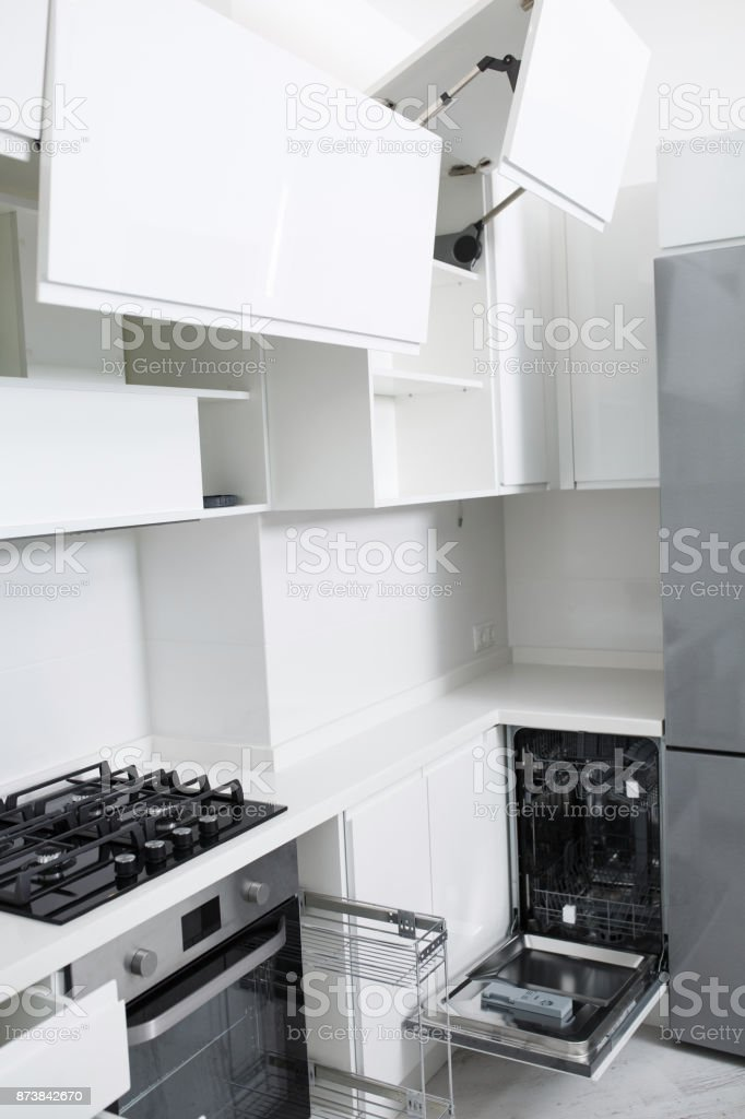 Design of a new light kitchen in pastel colors. There is a dishwasher in the kitchen stock photo