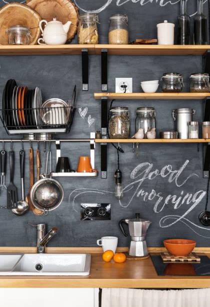 """design moderne küche im loft und rustikalen stil. holzregale mit verschiedene gläser auf eine schwarze wand mit kreide """"guten morgen"""" - küche rustikal gestalten stock-fotos und bilder"""