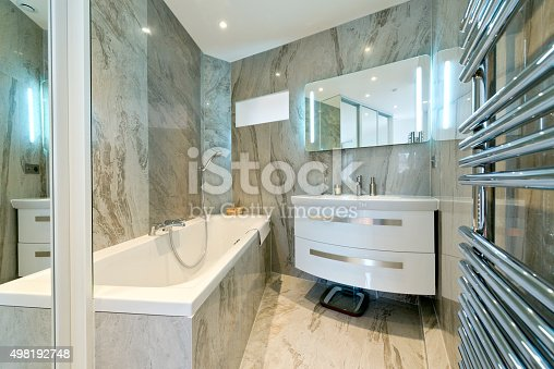 Modern style interior design of a bathroom . Luxury bathroom estate home shower. Bathrooms tastefully decorated with bath, wash basin, mirror and shelves in light colors.