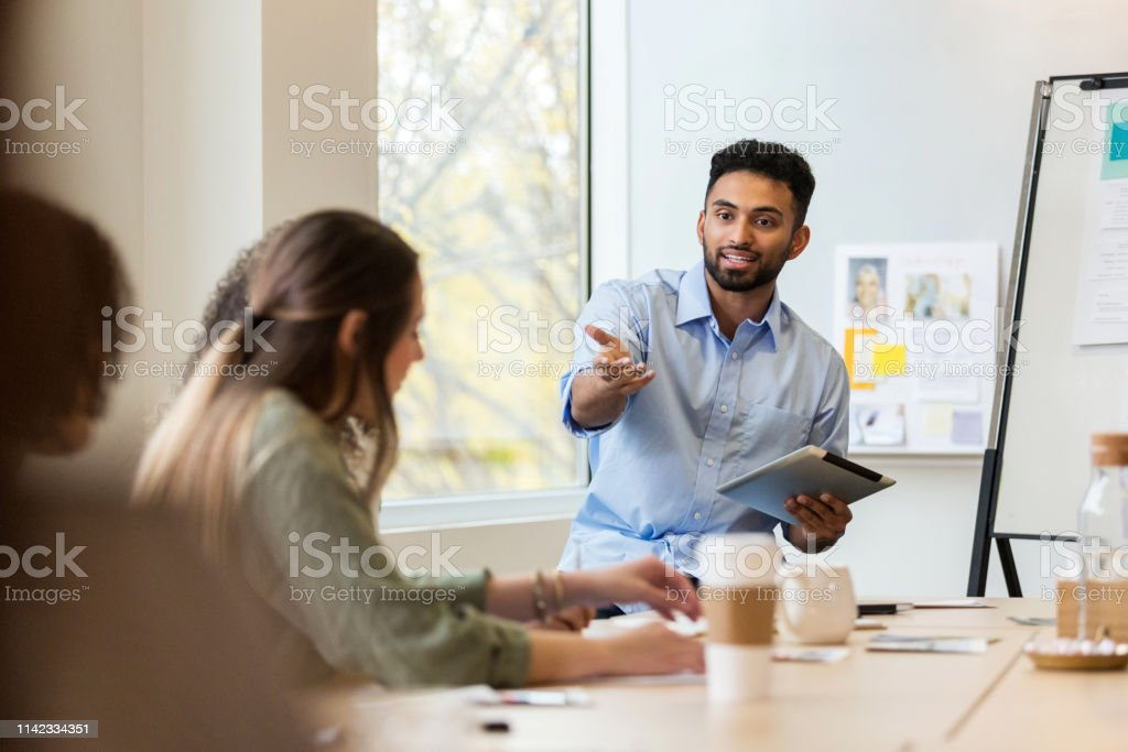 A young male design professional leads a meeting. He gestures toward...