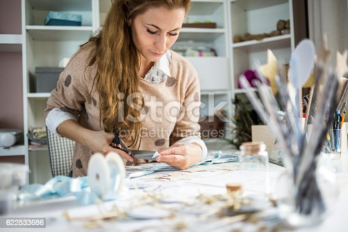Artisan woman cutting paper in her atelier, small business owner