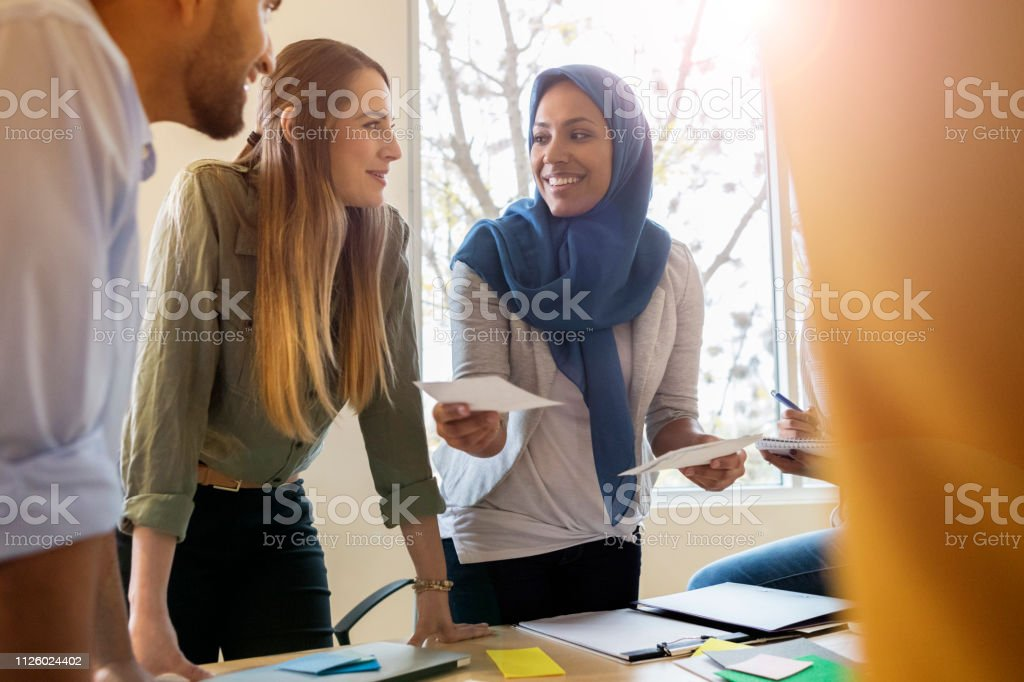 A smiling Muslim female design professional stands around a table...