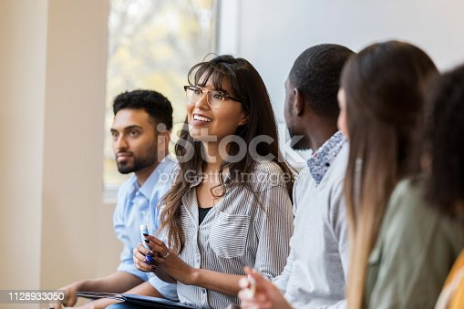 A cheerful young woman speaks during a design professionals training class.  She is sitting in a row with classmates.