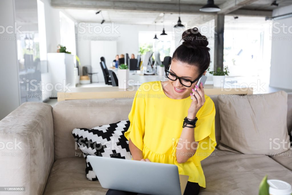 Design professional working at office Female design professional talking on mobile phone while sitting with laptop in office 20-24 Years Stock Photo