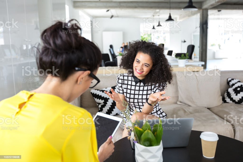 Design professionals discussing in office Two women working in office and discussing work. Smiling woman talking with female colleagues using digital tablet in creative workplace. 20-24 Years Stock Photo