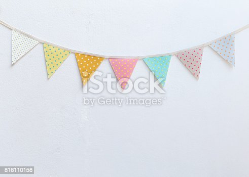 istock Design vintage fabric party flag over white cement wall texture background 816110158
