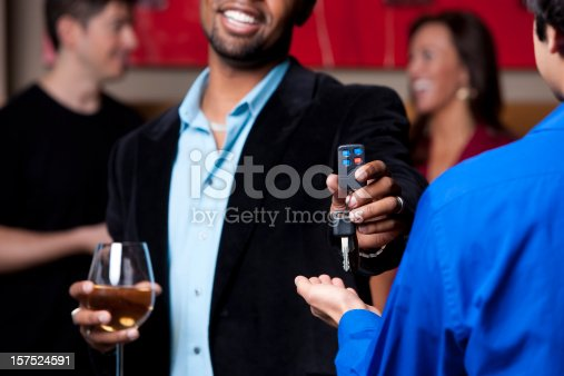 An african american male hands over the keys while holding a glass of wine at a party.
