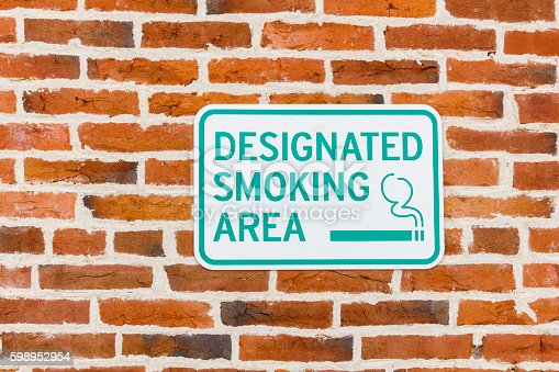 A sign letting people that smoking is allowed in this immediate area.  The designated smoking area sign is secured to a red brick wall.