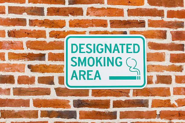Designated Smoking Area Sign On a Red Brick Wall stock photo