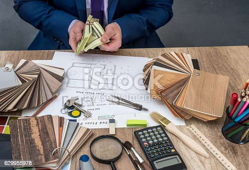 istock Designer counts the money for the work - house project. 629955978