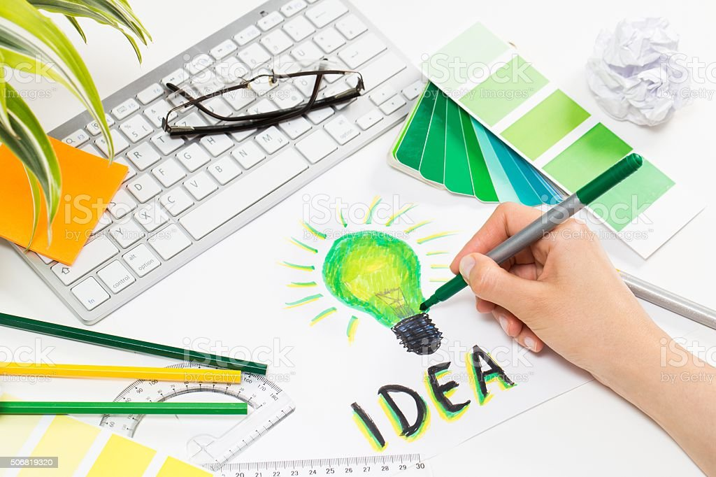 Designer drawing a light bulb. Brainstorming cocnept. stock photo