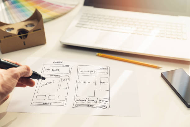 designer drawing website development wireframe on paper stock photo