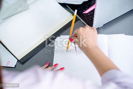 istock Designer draws at desk in office, with pencil and divider. 1126581057