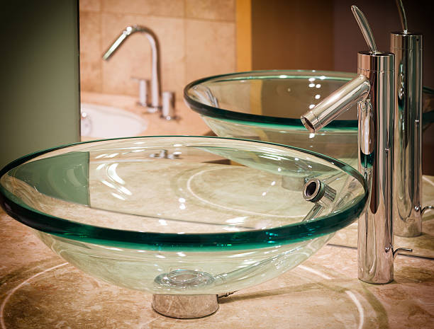 Designer glass wash basin and chrome faucet. stock photo