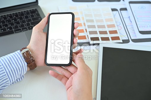 995213208 istock photo UX UI designer holding blank screen mobile phone 1053484360
