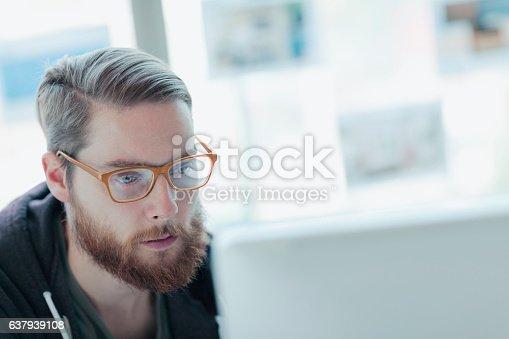 istock Designer looking at computer in studio office 637939108