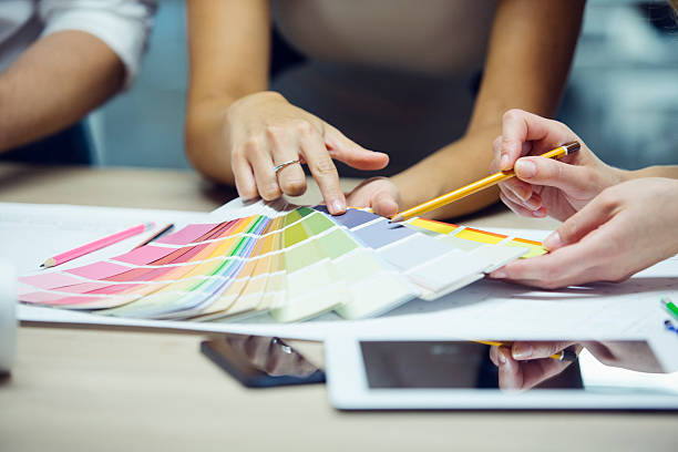 Designer pointing to color swatch. Closeup of interior designers or architects hands pointing to colour swatch. interior designer stock pictures, royalty-free photos & images