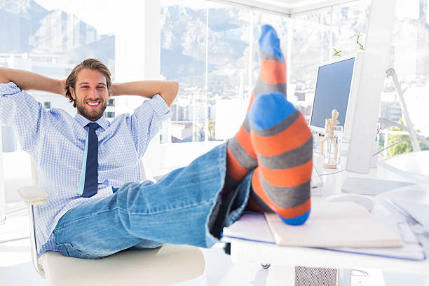 Designer relaxing at desk with no shoes and smiling stock photo